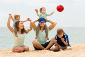 Familia de viaje jugando en la playa de vacaciones
