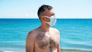 Hombre con mascarilla en la playa verano España