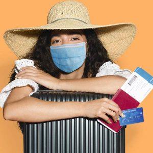 Mujer preparada para irse de vacaciones de verano con mascarilla